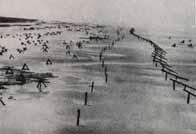Une plage en Normandie peu de temps avant le débarquement. On peut remarquer des rampes, des pieux ainsi que des tétraèdres doublés de mines
